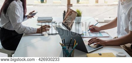 Business People Meeting Using Laptop Computer,calculator,notebook,stock Market Chart Paper For Analy
