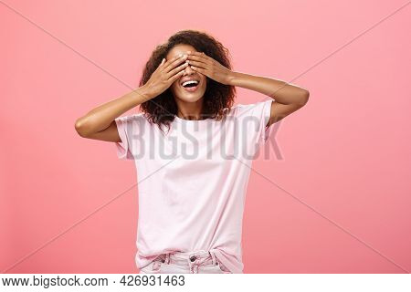 Portrait Of Charming Joyful Dark-skinned Playful Woman With Curly Hair In T-shirt Closing Eyes And C