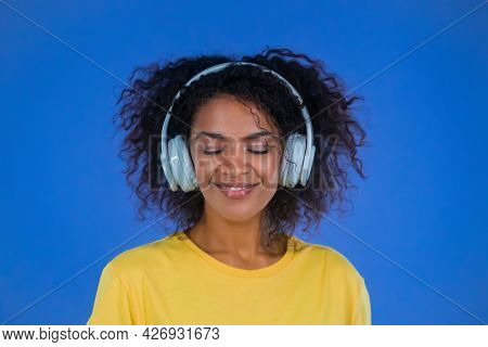 Attractive Woman Dancing With Wireless Headphones On Blue Studio Background. Cute African American G
