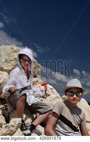 Boys Are Looking For Fossils In A Pile Of Limestone Stones. A Sunny Summer Day.
