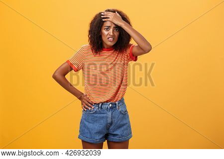 Shit I Am In Trouble. Concerned Anxious Cute Dark-skinned Woman In Trendy T-shirt And Shorts Clenchi