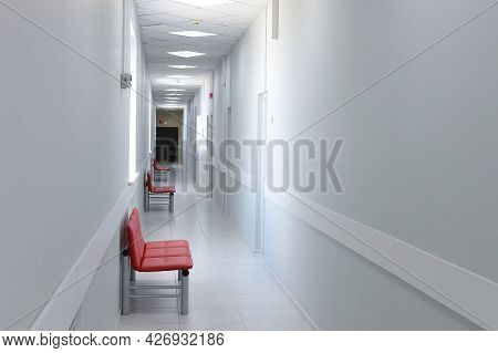 Empty Modern Hospital Corridor, Clinic Hallway Interior Background With Red Chairs For Patients Wait