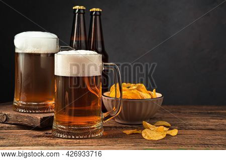Two Glasses Of Frothy Beer, Chips And Beer Bottles On A Brown Background. Side View, Space For Copyi