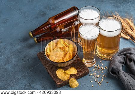 Beer Mugs And Bottles, Chips And Wheat On A Dark Background. Horizontal View, Space For Copying. Bee