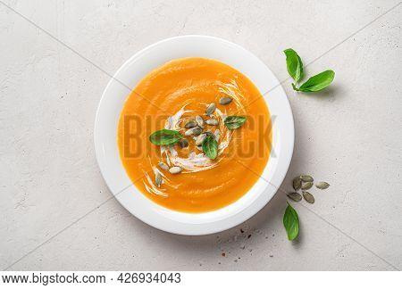 Pumpkin Cream Soup With Basil, Cream And Pumpkin Seeds On A Gray Background. Top View, Close-up.