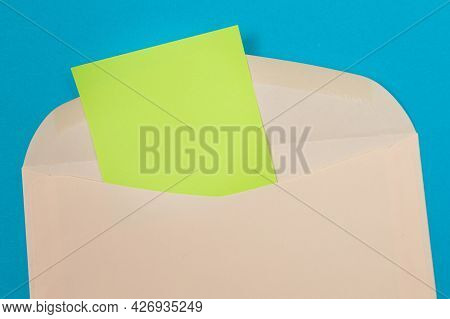 Beige Envelope With Blank Green Sheet Of Paper Inside, Lying On Blue Background - Mock Up With Copy