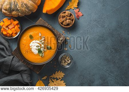 Pumpkin Cream Soup In A Black Bowl On An Autumn Background. Top View, Copy Space.