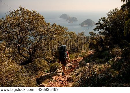 Rear View Of Male Tourist With Backpack. Hike Along The Lycian Trail