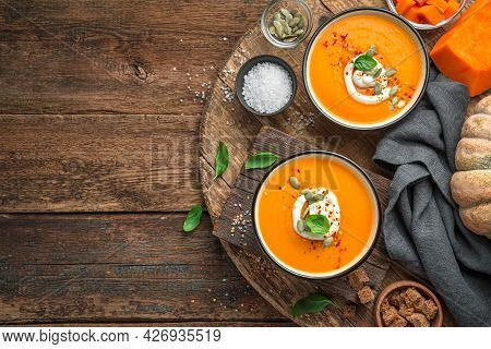 Two Bowls Of Pumpkin Cream Soup With Basil, Cream And Pumpkin Seeds On A Brown Background. Top View,