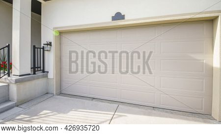 Pano Exterior Of A House With Closed Garage Door And Part Of A Porch Entry With Stairs