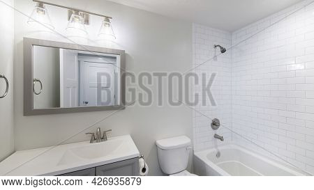 Pano Interior Of A Bathroom With Vanity Sink And Shower Tub Combo With Subway Tiles Wall Surround