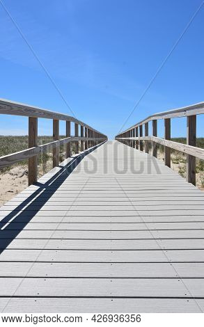 Long Perspective Of A Wood Boardwalk Over Beach Sand Dunes.