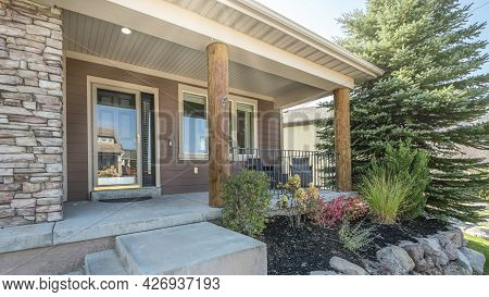 Pano Front Exterior Of A House With A Raised Edge Landscape And Stone Brick Walls