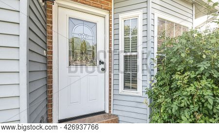 Pano Front Door Exterior With Bricks And Vinyl Siding Wall