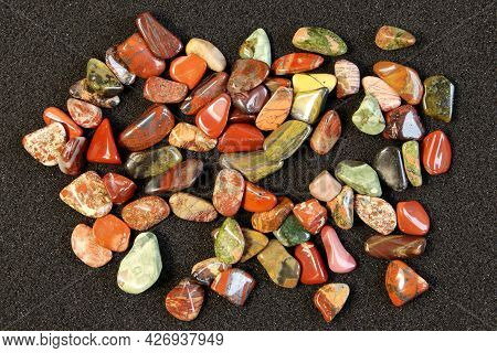 Red And Multicolored Jasper Polished Tumblestones On Black Background Top View
