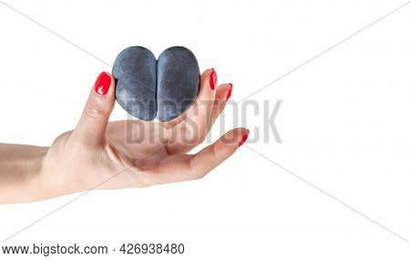 A Hand Holds A Plum With A Heart Shape Isolated On A White Background. Ugly Food. Food In Heart Shap