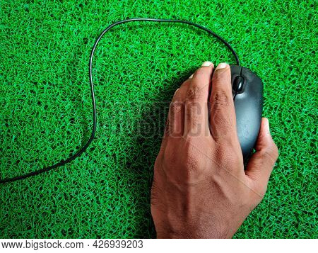 Top View Of Male Hands Clicking Wired Black Color Computer Mouse. Isolated On Green Background