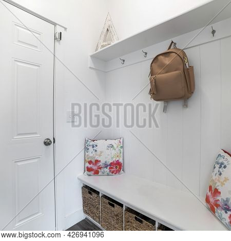 Square Frame Interior Of A White Mud Room With White Door, Built-in White Bench And Wall Mounted Hoo