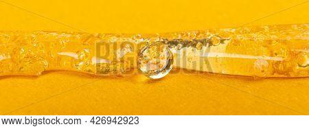 Pure Clear Marijuana Wax On Yellow Background, Cannabis Dab Texture.