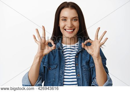 No Problem, Yes Its Alright. Smiling Young Woman Looks Satisfied, Shows Okay Zero Ok Gesture, Nod In
