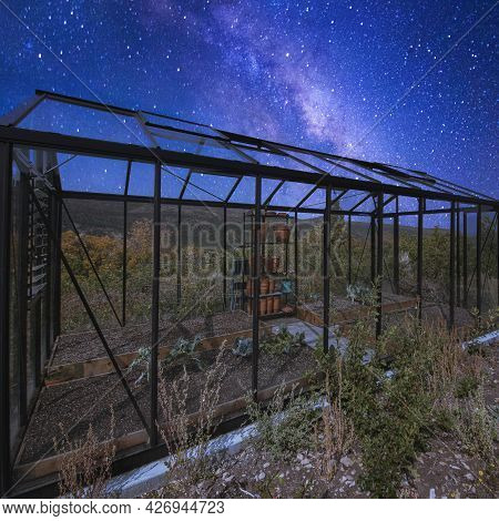 Square Frame Glass Greenhouse At The Back Of A House Under A Stunning Composite Milky Way Sky