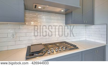 Pano Cooktop Stove Fixed On Kitchen Countertop With Exhaust Hood And Gray Cabinets