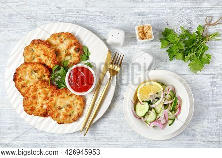 Cheesy Chicken Fritters, Chicken Breast Patties Served With Tomato Sauce On A White Plate And Cucumb