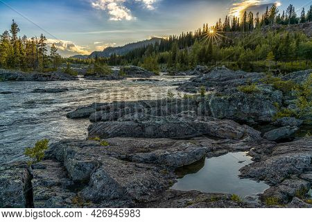 An Idyllic River And Pine Forest Landscpe With A Setting Sun And Sun Star And A Heart-shaped Pool In