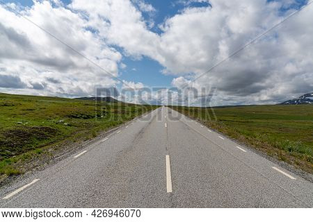 A Paved Highway Leads Straight To The Horizon In A Wild Tundra Landscape