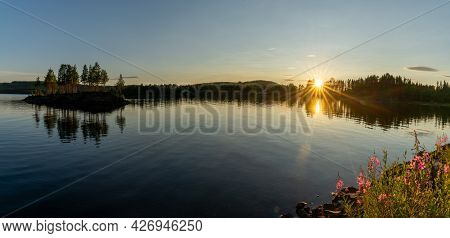 Panorama Of A Calm Lake With Small Island And Golden Sunset Evening Light On The Trees And Forest On