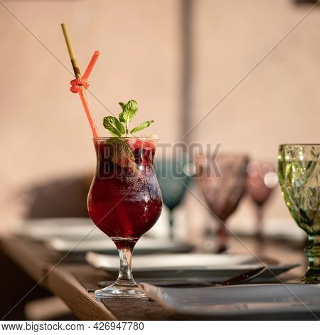 Red Berries Drink With Mint Sprig On Sunny Blurred Background. Glass Of Refreshing Drink With Straws