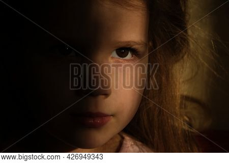 Little Girl In Dark Side With Shadow On Face With Blissful Eyes  Looking  Dreaming Or Praying.  Soft