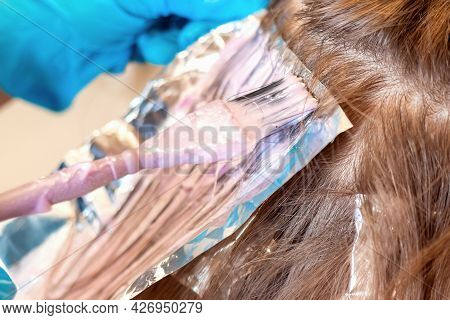 Close-up And Soft Focus Of Strand On Head On Special Sheet Of Foil, Which Is Applied To Hair Dye Wit