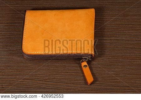 Brown Leather Wallet Closed With Zipper On Wooden Table