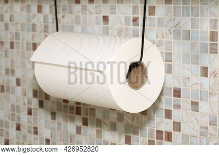 White Paper Towel Roll Hanging On A String In Kitchen