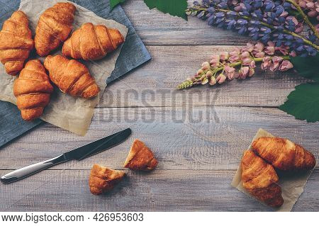Freshly Baked Croissants Wrapped In Wrapping Paper On A Wooden Table For Breakfast. Dark Background.