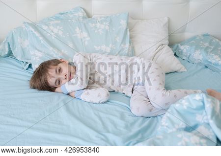 Caucasian Boy In Pajamas Sleeps In The Morning On The Bed. Top View. The Child Wakes Up With A Smile