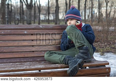 Caucasian Boy On A Walk In The Park Sits Alone On A Bench. Sad And Sad Child. The Concept Of The Rel