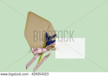 Bouquet Of Tender Hyacinths Tied With Pink Ribbon And Brown Craft Envelope With Paper Sheet, On Gree