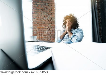African American Businessman Sitting At The Table And Working At The Laptop Weary Touching His Face