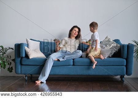 Tired Young Mother Or Nanny Resting On The Couch Wants To Relax At The Phone But The Child Needs Att