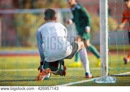 Adult Football Goalkeeper Player Catching Ball In A Goal. Soccer Player In A Game. Goalie In Action.