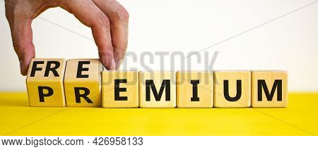 Premium Or Freemium Symbol. Businessman Turns Wooden Cubes And Changes The Word 'premium' To 'freemi