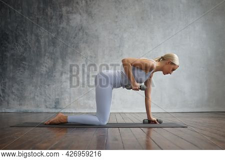 Young And Sporty Girl In Sportswear Is Doing Exercises In Home Interior. Fit And Slender Blond Woman