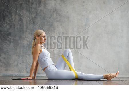 Young And Sporty Girl In Sportswear Is Doing Exercises In Home Interior Using Resistance Band. Fit A