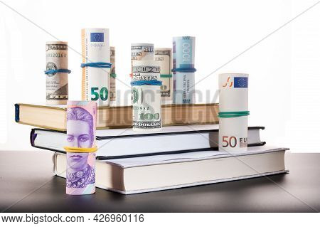 Diverse Currency On The Steps. Hierarchy Of Money. Money And Books Isolated.