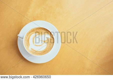 Cup Of Coffee With Latte Art On A Wooden Table In A Cafe. Flat Lay. Place For Text.