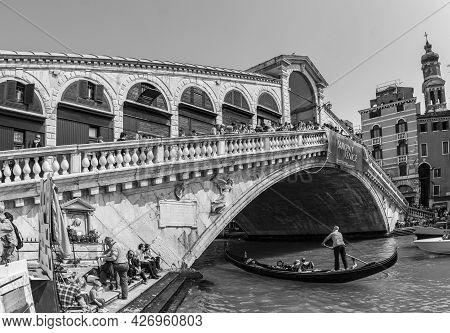 Venice, Italy - April 7, 2007: Tourists Ride On Boat Under The Rialto Bridge In Venice, Italy. Rialt
