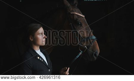 Horsewoman Posing With Her Seal Brown Horse Holding Its Bridle. The Girl Is Dressed In A Black Coat.