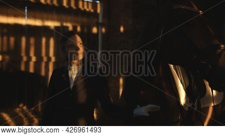 Female Horse Owner Standing With Her Seal Brown Horse In The Stable. Horse Wearing Head Jewelry. The